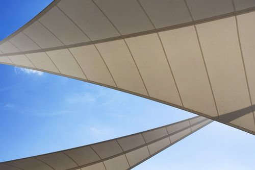 Bottom view of triangle shaped big sun shades and clear blue sky